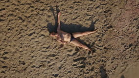The man in starfish pose lays on sand and sunbathe. Handsome young man lays on the sand in starfish pose. The man is sunbathing and looking in camera. Camera stock video footage