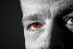Man Staring. A semi-monochromatic image of a middle aged man staring at you from the shadows Royalty Free Stock Photo