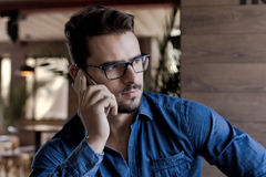 Man staring aside and using mobile phone Royalty Free Stock Photos