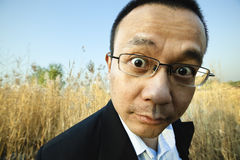 Man staring at camera. Outdoor portrait of an asian businessman staring at camera, wide angle lens Royalty Free Stock Photos