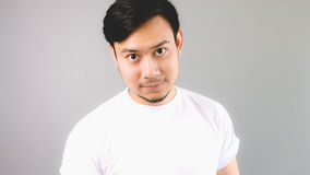 A man staring at the camera. An asian man with white t-shirt and grey background royalty free stock photography