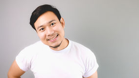 A man staring at the camera. An asian man with white t-shirt and grey background stock photography