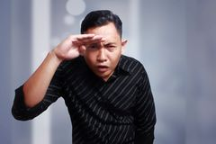 Man Staring and Looking Far Away, Looking at Camera. Funny Asian man curious staring and looking far away to the front direction, looking at camera Royalty Free Stock Image