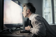 Man staring at the screen. Of a computer Stock Image