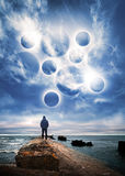 Man starring at the planets in dramatic blue sky Stock Photos