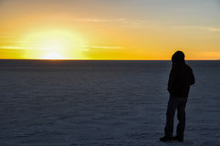 Man starring at the sunset in Salar de Uyuni, Bolivia Stock Photo