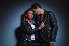 The man in starring at the woman while she is pulling his jacket. Portrait of punk couple in leather posing in dark studio background. the men in starring at the Stock Images