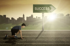 Man in start position with success signpost. Young man in start position to run in the track with success word on signpost Royalty Free Stock Images
