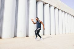 Side view of cut Black athlete sprinting on the street. Man start running on the pathway with the blue sky in the background and copy space around him. Motion stock photography