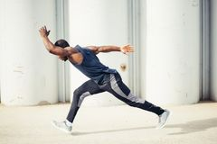 Side view of cut Black athlete sprinting on the street. Man start running on the pathway with the blue sky in the background and copy space around him. Motion Stock Images