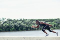 Side view of cut Black athlete sprinting on the street. Man start running on the pathway with the blue sky in the background and copy space around him. Motion royalty free stock photo