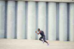 Side view of cut Black athlete sprinting on the street. Man start running on the pathway with the blue sky in the background and copy space around him. Motion royalty free stock photography