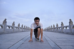 A man start to run. On a traditional bridge of china Stock Image