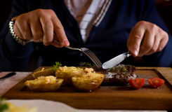 Man started eat medium roasted veal steak . Hands close-up view. Stock Image