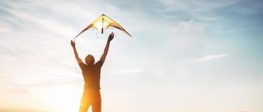Man starten för att flyga en drake i himlen royaltyfri foto