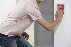 Man Starting Fire Alarm Stock Photos