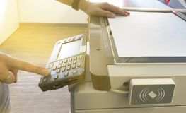 Man starting to copy document from a Photocopier with a scanning key card panel. royalty free stock photos
