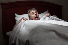 Man startled awake by intruder Royalty Free Stock Image