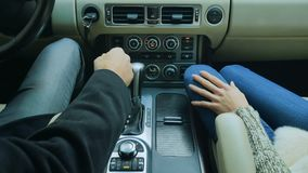 Man starts the car and puts his hand on hand of his girlfriend stock video footage