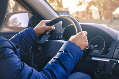 Man starts driving a car. Hand are on wheel. Sunny day Stock Photos