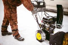 Man starts engine snow blower stock photos