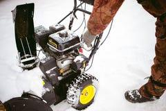 Man starts engine snow blower. Man starts the engine snow blower royalty free stock photo
