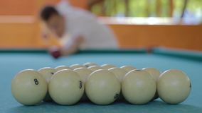 A man starts a game in Russian billiards. The player breaks the pyramid from the balls stock video