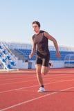 Man starts running. A young man starts running in the stadium. Treadmill Stock Photography