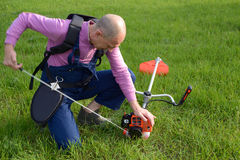Man starts a weed trimmer Stock Photo
