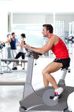 Man on stationary bicycle at sport fitness gym. Interior Royalty Free Stock Photography
