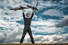 Man stay with bicycle overhead in nature blue sky royalty free stock photo
