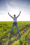 Man stay in green field with hands up Stock Images