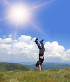 Man stay head over heels. On meadow in mountais royalty free stock images