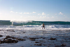 Man stay in the rock beach and look on big waves. Sunny day. Royalty Free Stock Photos