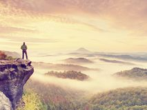 Man stay on rocky peak within daybreak and watch over misty landscape. Stock Image