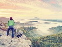 Man stay on rocky peak within daybreak and watch over misty landscape. stock photo