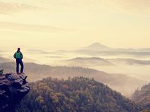 Man stay on rocky peak within daybreak and watch over misty landscape. Royalty Free Stock Photos