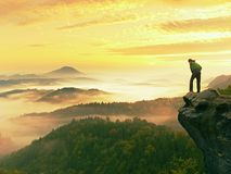 Man stay on rocky peak within daybreak and watch over misty landscape. Stock Images
