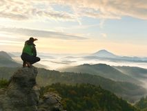 Man stay on rocky peak within daybreak and watch over misty landscape. Stock Photos