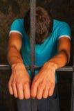 Man behind the bars. Man staying behind the bars royalty free stock photography