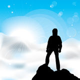Man staying on a top of a mountain. A silhouette of man staying on a top of a mountain and sun rays Royalty Free Stock Photo