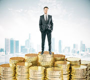 Man stays on piles of coins concept at city background Stock Images