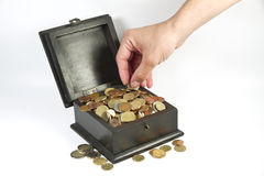 A man stealing coins from a box Stock Image