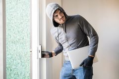 Man stealing stuff from a house. Hispanic male criminal stealing a laptop computer and walking away unnoticed Royalty Free Stock Photos