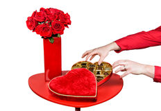 Man Stealing Valentines Chocolates. A table is set up with a red vase with red roses beside an open heart shaped box of chocolates.  A mans hands are shown about Stock Images
