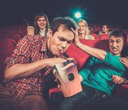 Man steals popcorn in cinema. Impudent young men steals popcorn in cinema while people watching movie stock photo