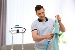 Man steaming his clothes in room stock image