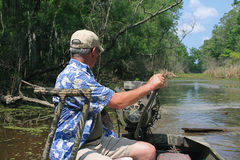Man steering boat in the Bayou. Man with hand on a tiller steering a mud motor down a canal.  Motor boat is followed by a wake in the water with green trees Stock Image