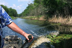 Man steering boat in the Bayou. Man with hand on a tiller steering a mud motor down a canal.  Motor boat is follow by a wake in the water with green trees, blue Royalty Free Stock Photography