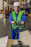 Man steering pallet truck in warehouse. Man with stubble wearing uniform and hardhat steering pallet truck carrying boxes in warehouse Stock Image
